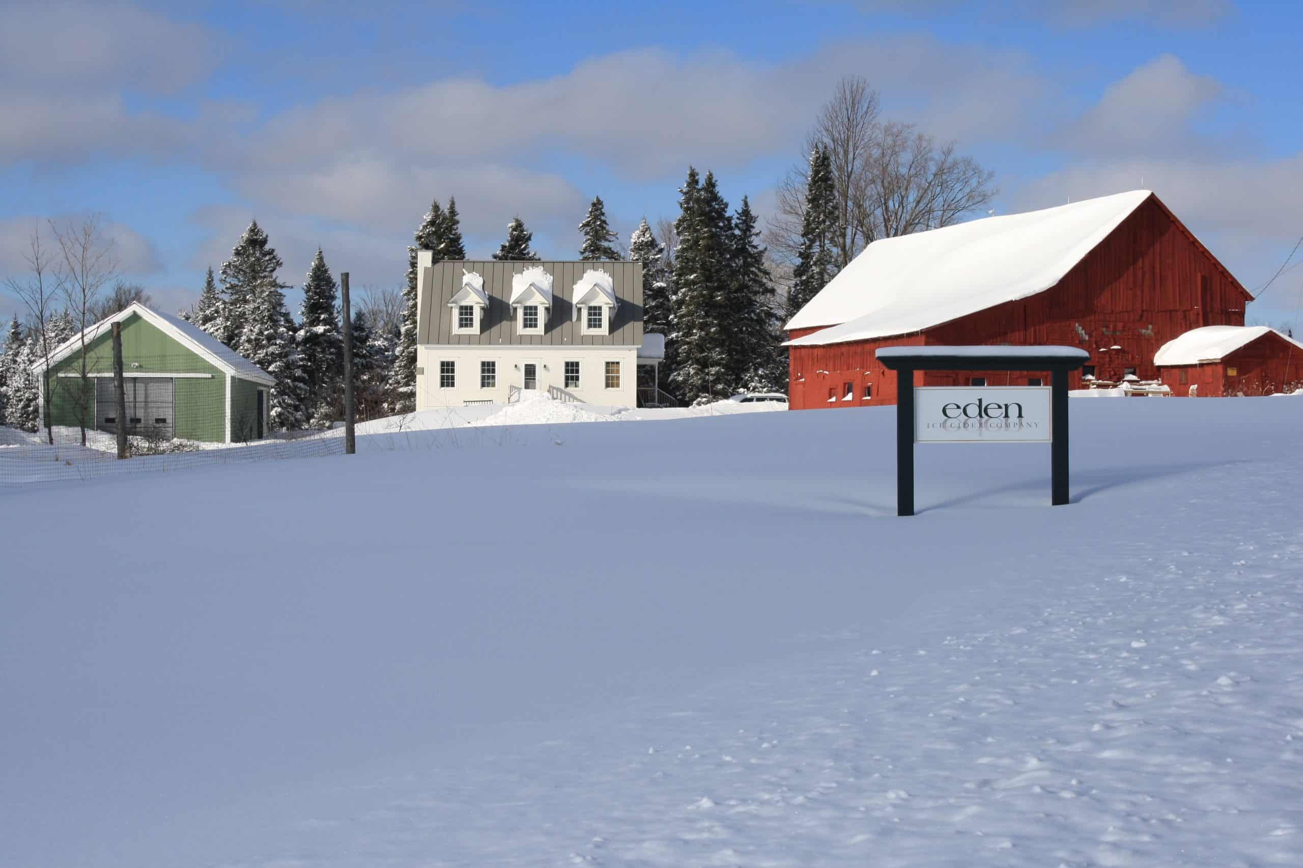red cider barn and white house in snow